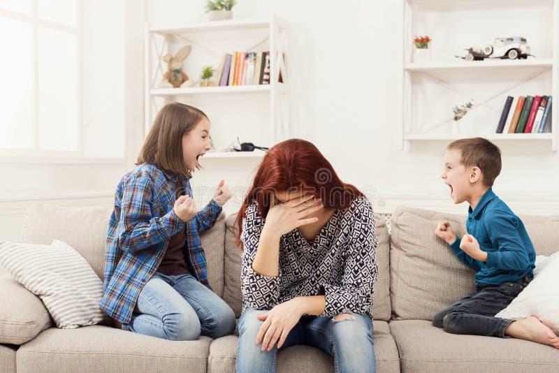 有的孩子在疲乏的母亲的争吵 库存照片