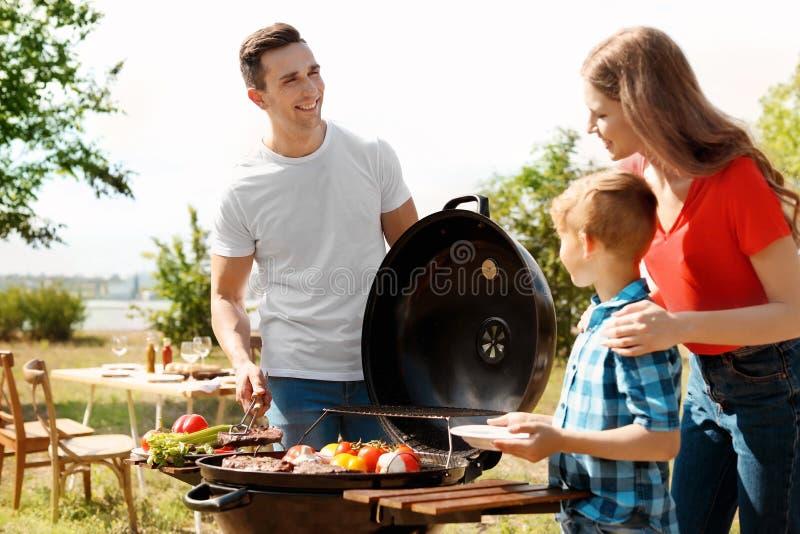 有的家庭与现代格栅的烤肉户外 免版税库存图片