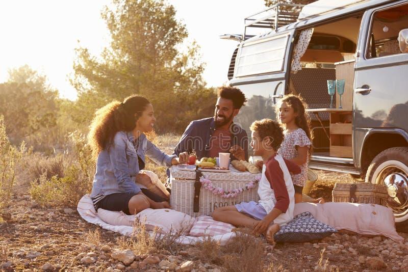 有的家庭在他们的露营者货车旁边的一顿野餐,全长 库存照片