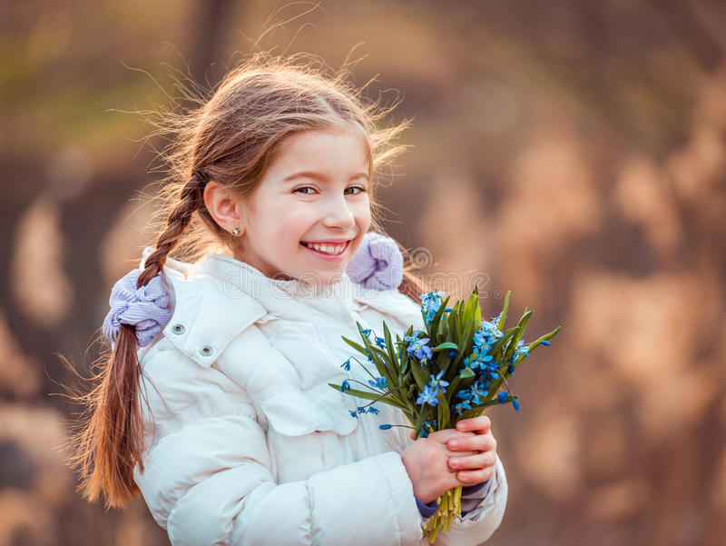 有的小女孩snowdrops 免版税库存图片