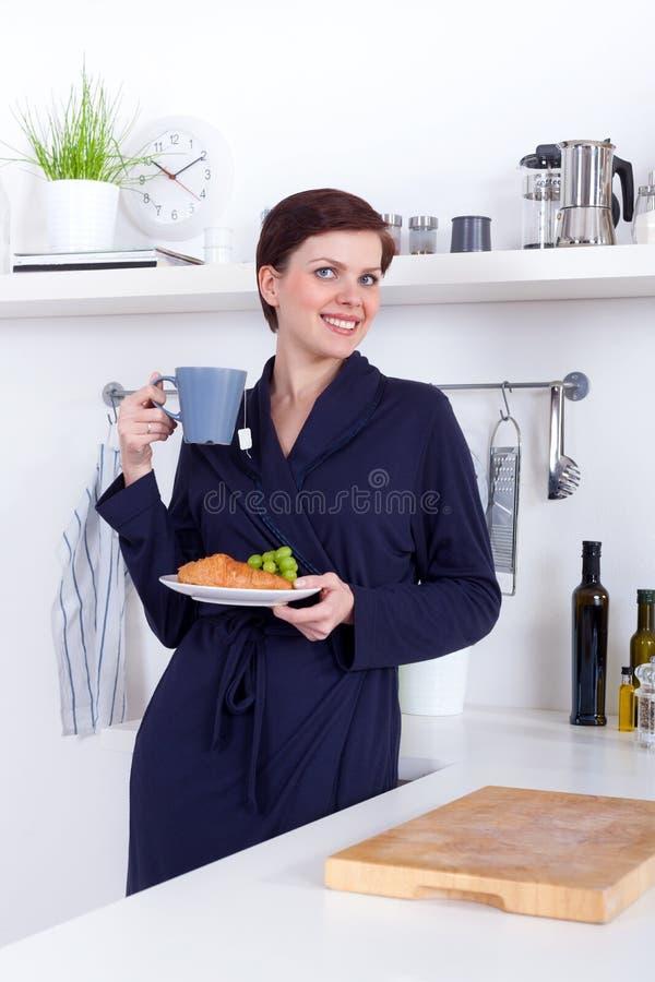 有的少妇一杯茶和健康早餐 图库摄影