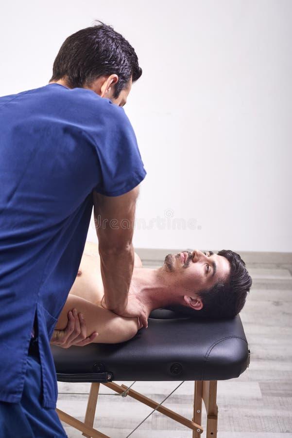 有的年轻人按摩脊柱治疗者肩膀调整 物理疗法,体育伤害修复 整骨疗法,替代医学, 库存图片