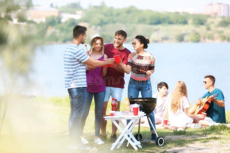 有的年轻人烤肉聚会在好日子户外 免版税库存照片