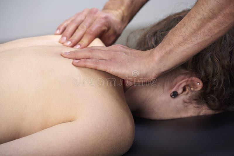 有的年轻女人按摩脊柱治疗者后面调整 物理疗法,体育伤害修复 整骨疗法,替代医学, 免版税库存图片