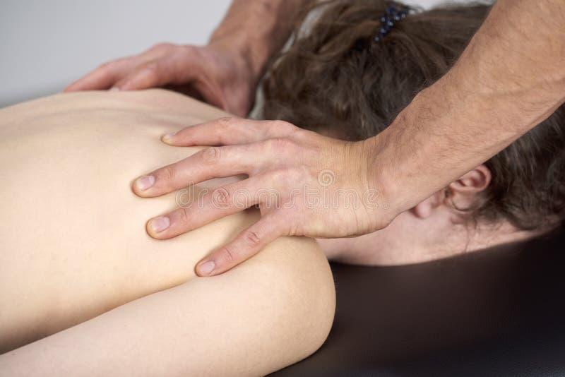 有的年轻女人按摩脊柱治疗者后面调整 物理疗法,体育伤害修复 整骨疗法,替代医学, 免版税图库摄影