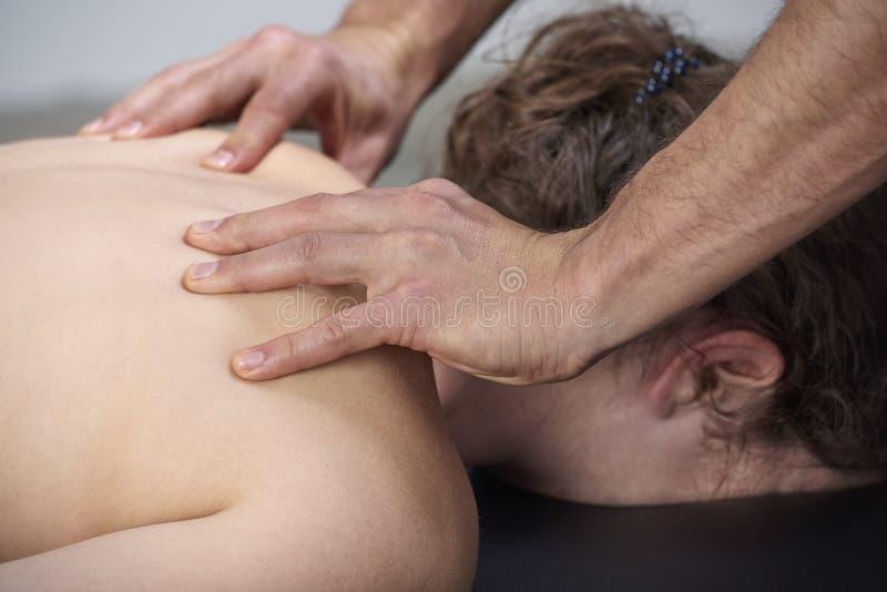 有的年轻女人按摩脊柱治疗者后面调整 物理疗法,体育伤害修复 整骨疗法,替代医学, 免版税库存照片