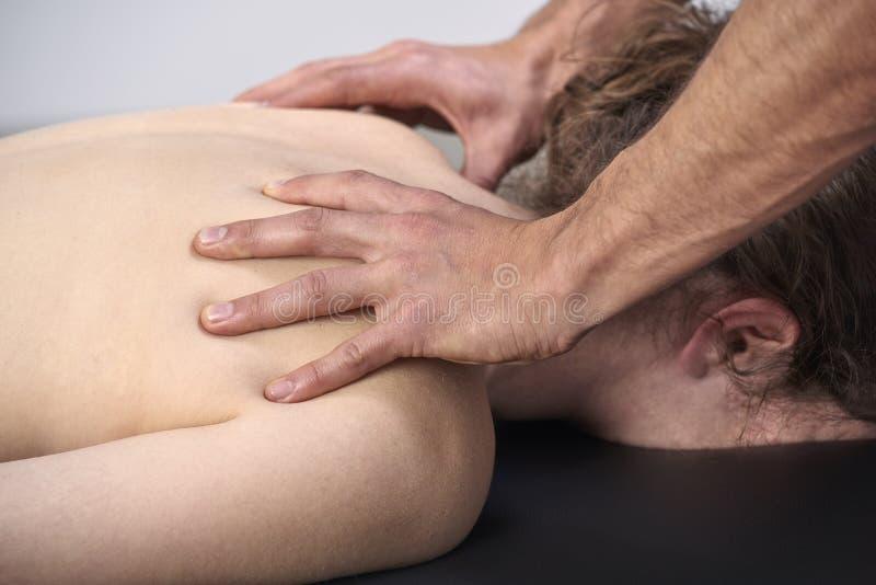 有的年轻女人按摩脊柱治疗者后面调整 物理疗法,体育伤害修复 整骨疗法,替代医学, 库存图片