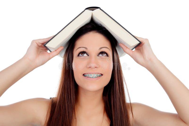 有的托架的可爱的学生妇女在头的一本书 免版税库存照片