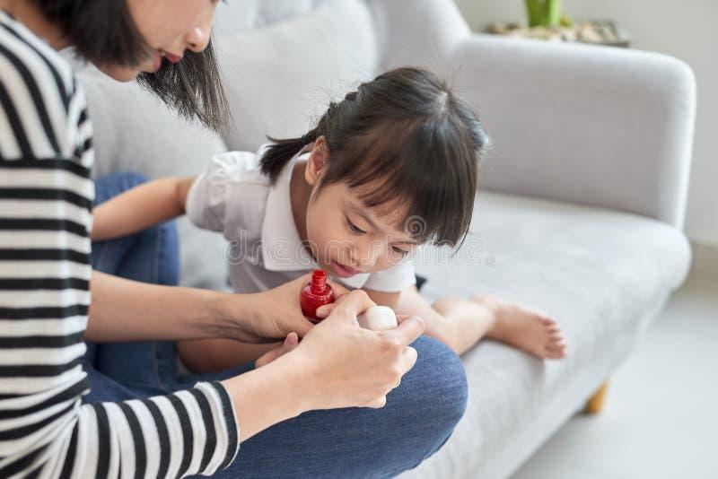 有的母亲和的女儿乐趣绘的指甲盖,家庭时间概念 免版税图库摄影