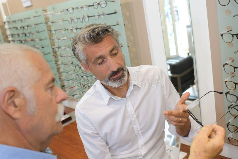 有的眼镜师与顾客的交谈 免版税库存图片