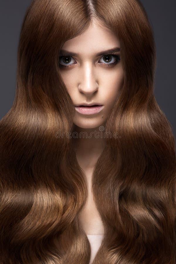 有的美丽的深色的女孩完全卷曲头发和经典构成 秀丽表面 免版税库存图片