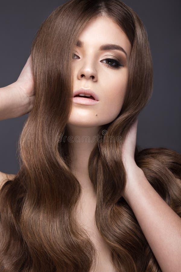 有的美丽的深色的女孩完全卷曲头发和经典构成 秀丽表面 免版税图库摄影