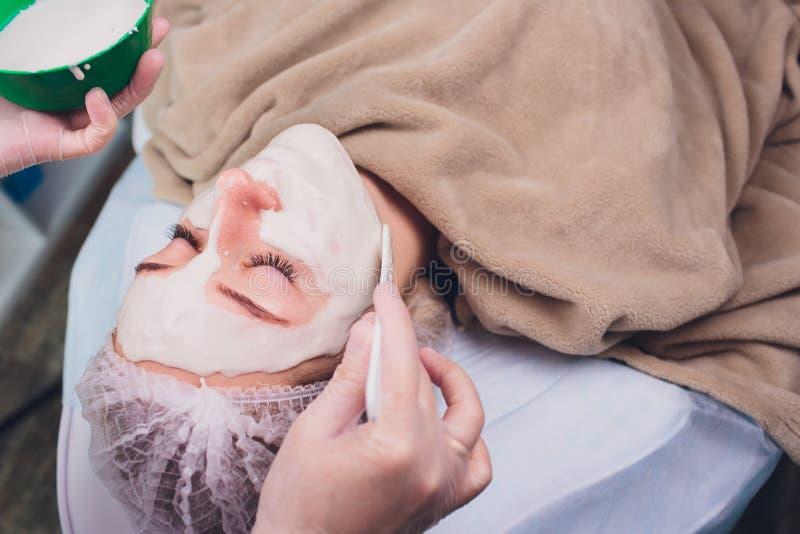 有的美女面部化妆用品洗刷从专业皮肤病学家的治疗在健康温泉 ?? 免版税库存照片