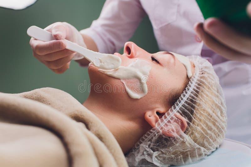 有的美女面部化妆用品洗刷从专业皮肤病学家的治疗在健康温泉 ?? 库存图片