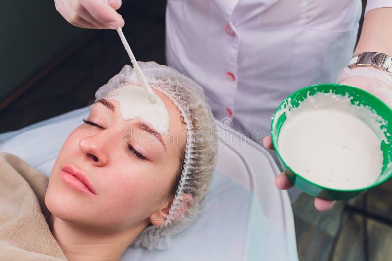 有的美女面部化妆用品洗刷从专业皮肤病学家的治疗在健康温泉 ?? 免版税图库摄影