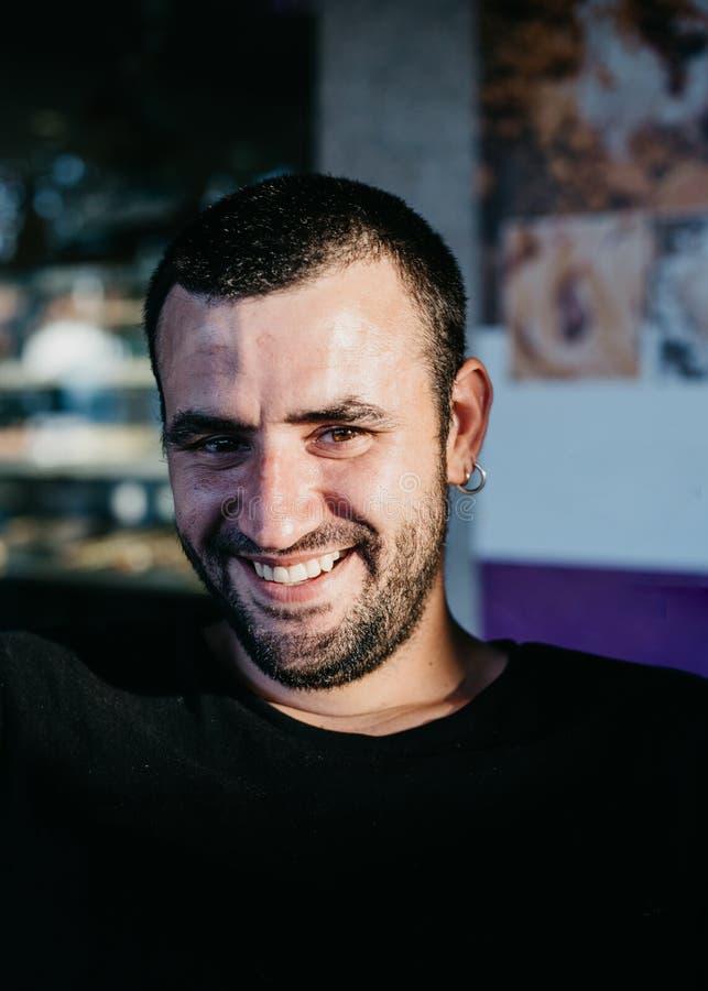有的英俊的微笑的有胡子的人在他的耳朵的耳环 免版税图库摄影