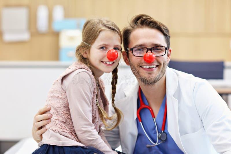 有的诊所的小女孩与儿科医生的核对 免版税图库摄影