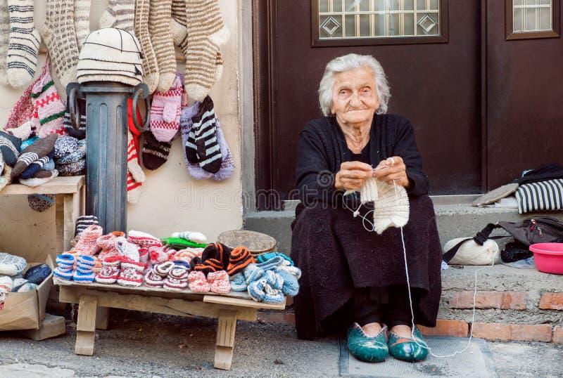 有的资深妇女坐家和编织针家庭的羊毛袜子门阶  库存照片