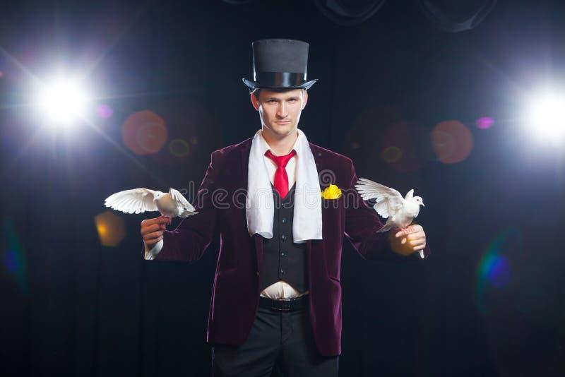 有的魔术师两只飞行的白色鸠 在黑色背景 免版税图库摄影