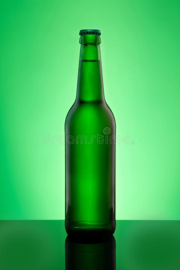 有皇冠盖的绿色啤酒瓶以垂直格式 免版税库存照片