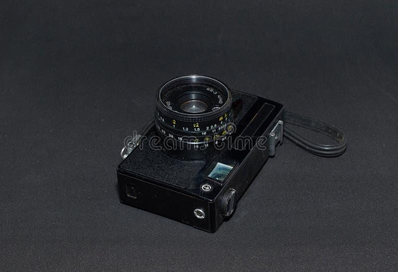 有皮带特写镜头的老胶卷相机在黑背景 免版税库存照片