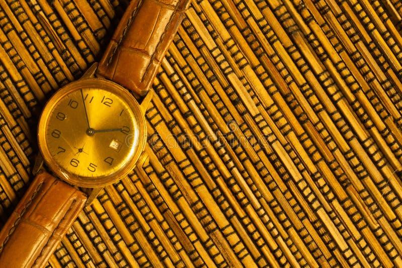 有皮带的葡萄酒金黄手表在竹背景 库存照片