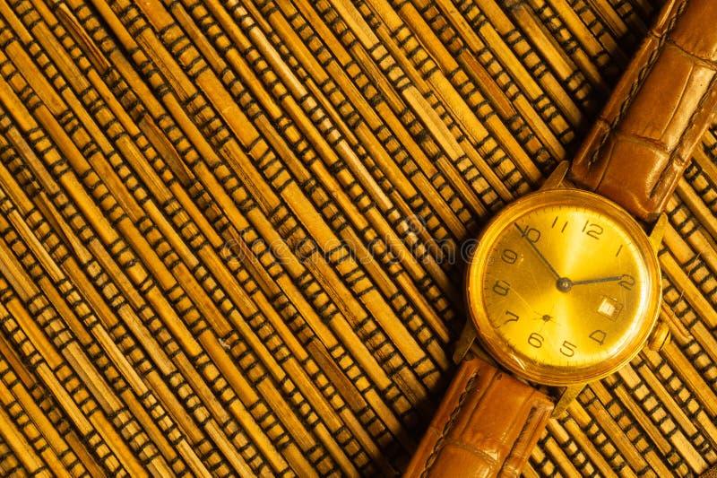 有皮带的葡萄酒金黄手表在竹背景 免版税库存照片