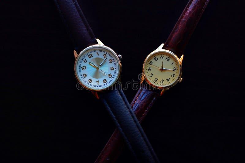 有皮带的金和石英手表在黑背景 库存图片