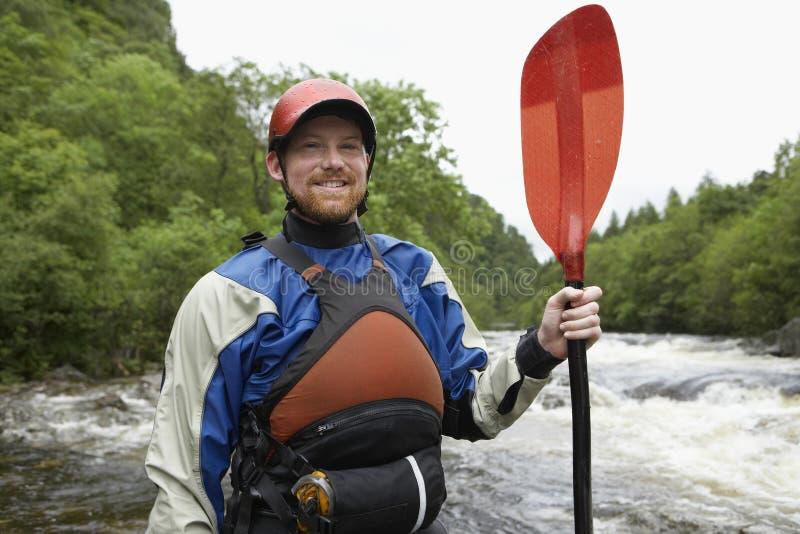 有皮船桨的人反对河 免版税库存照片