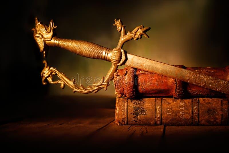 有皮革书的老剑在木桌上 免版税库存图片