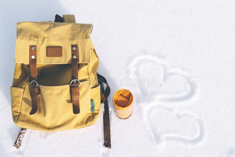 有皮革元素的橙色背包和热的茶或咖啡黄色热水瓶在白色纯净的雪背景在冬天登上 免版税库存图片