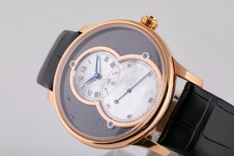 有皮革黑皮带的精神手表与银色拨号盘,黑数字和蓝色顺时针隔绝在白色背景 库存图片