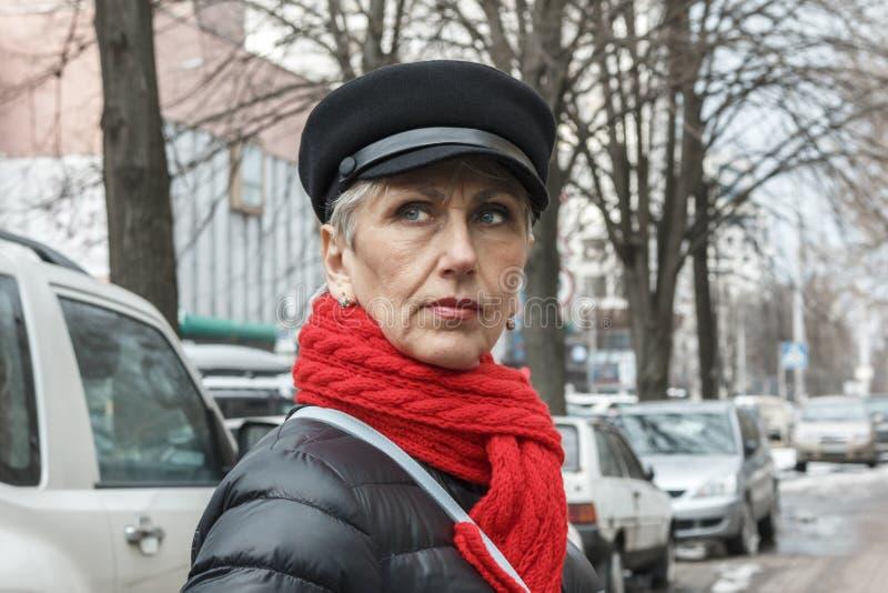 有皱痕的严肃的中年妇女在面孔和红色围巾 C 免版税图库摄影