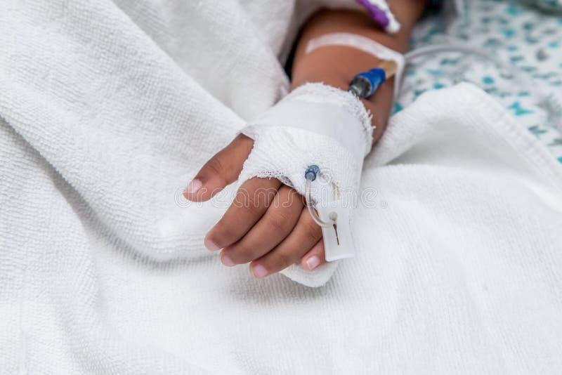 有盐静脉注射(iv)滴水的儿童的耐心手 免版税库存照片