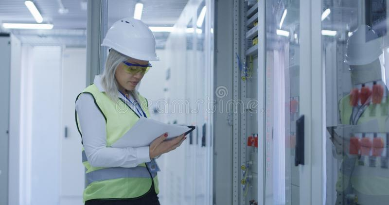 有监测电机工程的片剂的妇女 免版税库存图片