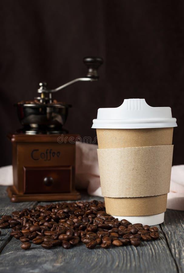 有盒盖的容器外带的咖啡的,在咖啡豆和磨房附近 免版税库存图片
