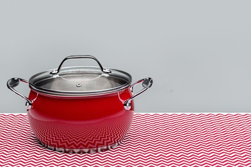 有盒盖的,在桌上的呈杂色的餐巾钢红色罐 免版税库存图片