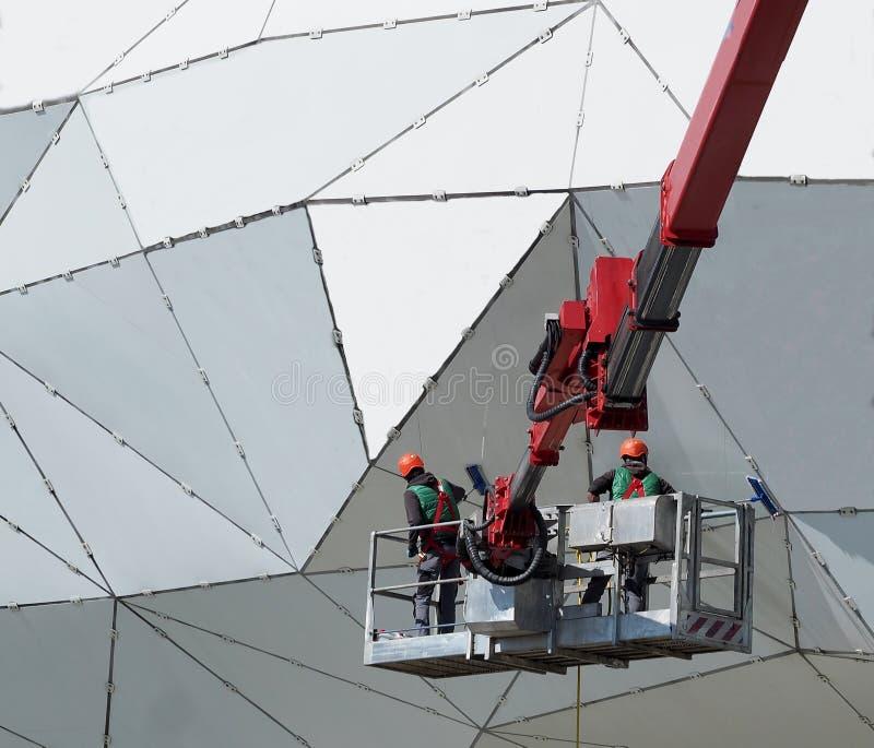 有盔甲的两名工作者和在樱桃捡取器的防护套服做清洁和维护在一个现代金属大厦之外 库存图片