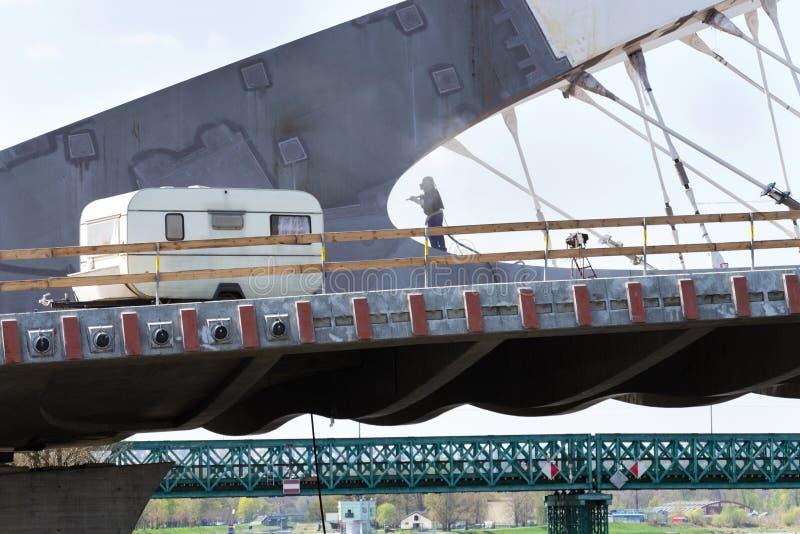 有盔甲的人象在桥梁建筑的机器人工作有在前景、机器人学自动化或者季节性工作的旅行拖车的 库存照片