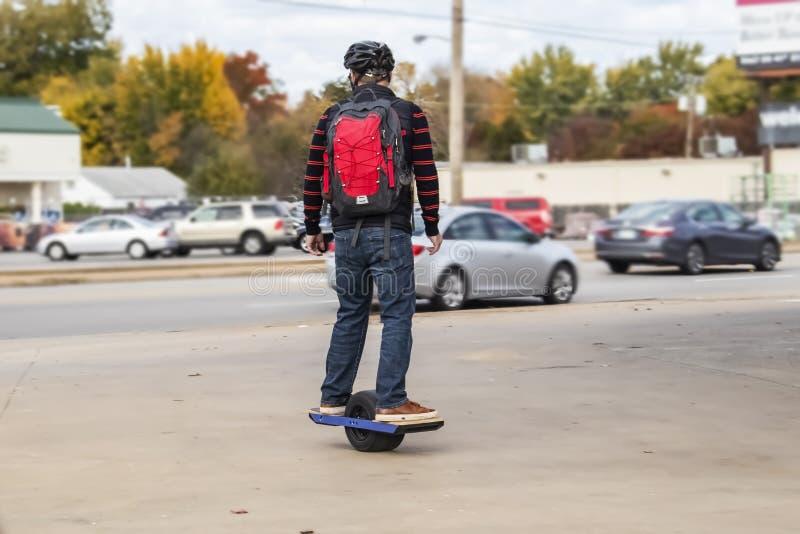 有盔甲的在一个轮子动力化的滑板的人和backback在边路在市区与在stree的汽车和商店和秋天 免版税库存照片