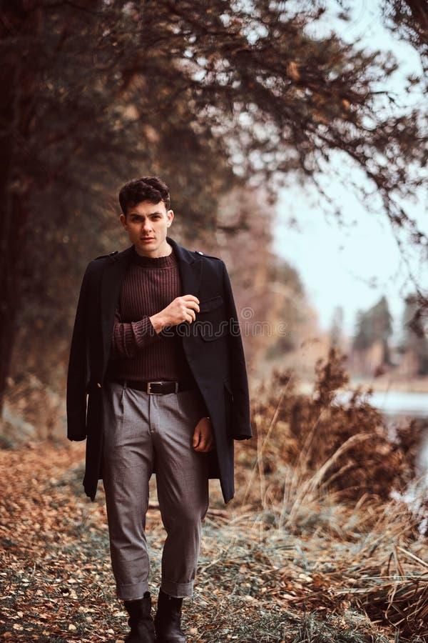 有盖他的肩膀的外套的年轻人在秋天森林里 库存图片