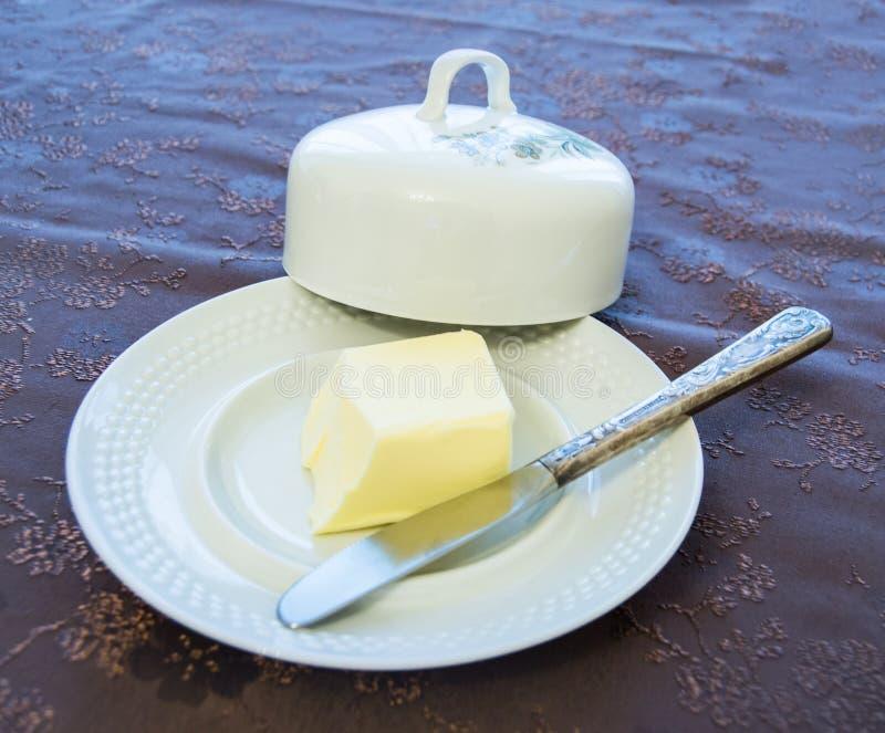 有盖子和银刀子的瓷板材用在装饰的盖子的黄油 库存图片