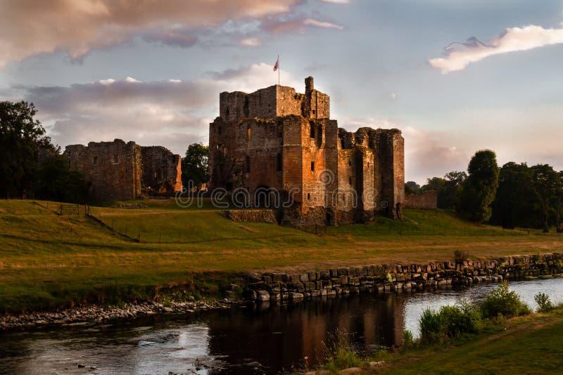 有盖马车城堡和小河废墟的壮观的看法在日落在Cumbria,英国 免版税库存图片