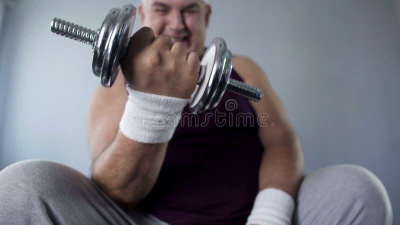 有目的肥胖人举的哑铃在家,努力工作丢失重量 库存照片