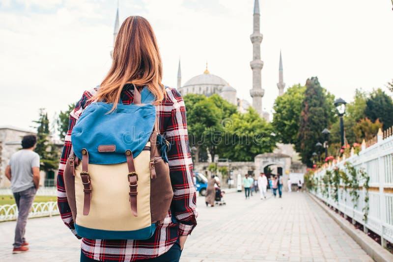 有看一个蓝色清真寺-伊斯坦布尔的一个著名旅游胜地的背包的年轻美丽的女孩旅客 旅行 图库摄影