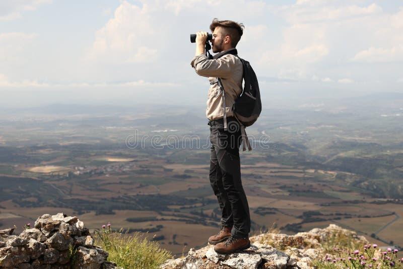 有看与从山的山顶的双筒望远镜的背包的登山人男孩在度假夏天休假 库存图片
