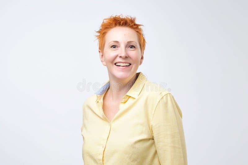 有看与快乐和迷人的微笑的红色头发的愉快的快乐的成熟妇女照相机 免版税库存照片