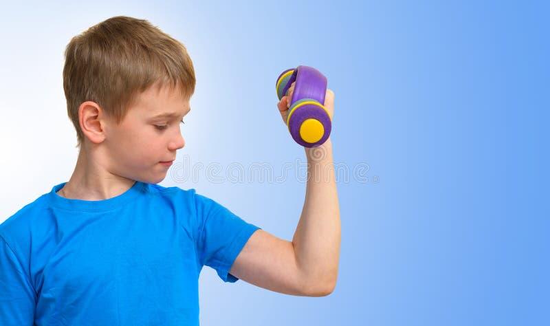 有看二头肌肌肉的哑铃的男孩 免版税库存照片