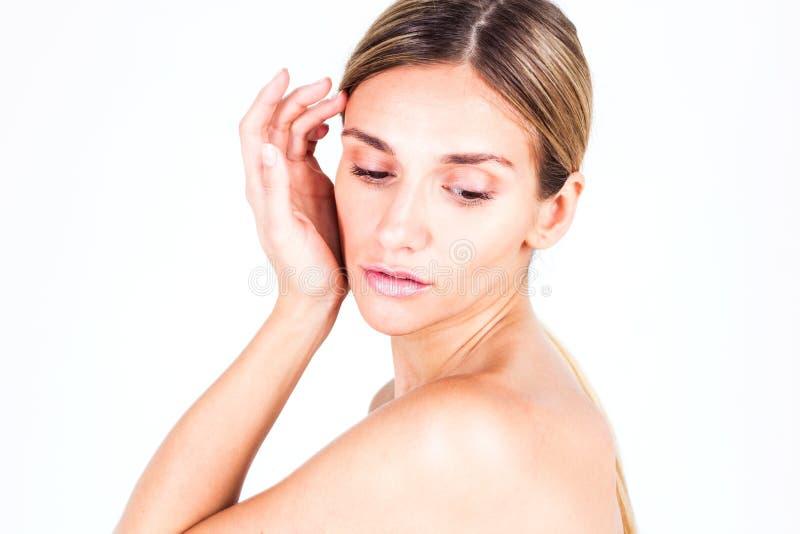 有看光滑的皮肤的少妇握她的手在面颊附近和下来 免版税库存照片