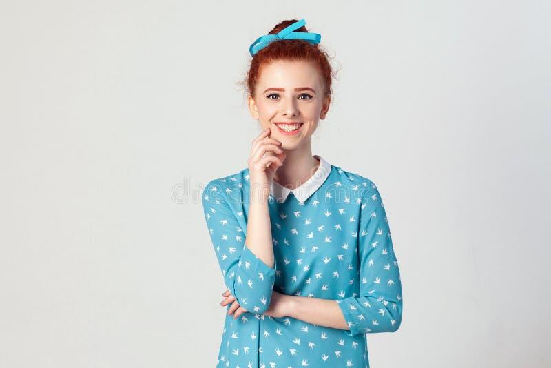 有看和微笑与愉快和快乐表示接触的照相机的完善的干净的皮肤的可爱的年轻红头发人女孩 库存图片